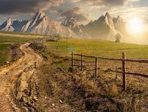 Road through rural fields in mountains at sunset. Road through rural fields in mountainous area. composite imagery of agricultural countryside in springtime at Royalty Free Stock Photography