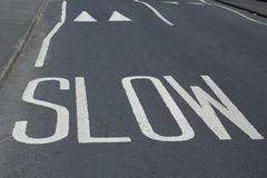 Road safety markings - slow. Painted road warning saying 'slow' and speed bumps Stock Images