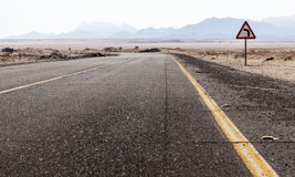 Road in the Sahara desert, Egypt. Asphalt road in the background of mountains in the desert Royalty Free Stock Photos
