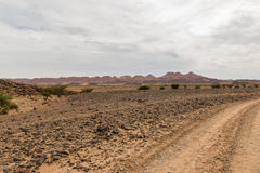 Road in Sahara desert. Road to the Sahara desert comes to mountains Stock Images