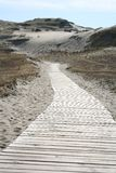 Road into the Sand. A road of planks going deep into the sand royalty free stock image