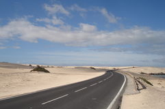 Road through the sands of the desert. A road like a serpentine through the desert of Fuerteventura Stock Photos