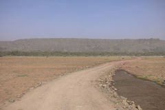 Road on savannah. Empty road on Safari in National Park Lake Manyara Conservation Area in Tanzania . Africa Stock Image