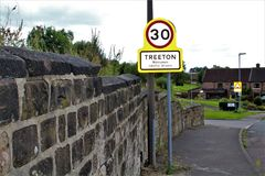 Road scape showing old stone wall and speed limit sign Stock Images