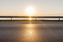 Road and sea in sunset time with burning sun Stock Images