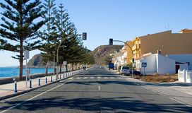 A road by seashore. A road in a small andalusian village with traffic lights, next to seashore Stock Image