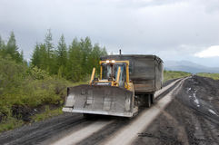 Road service tractor at gravel road Kolyma to Magadan highway Ya. Kutia, outback of Russia Royalty Free Stock Photo