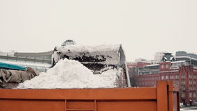 Road services clean sidewalks. Winter snow machine unloads the snow in truck body stock video footage