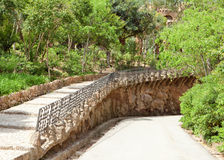 The road shielded by a handrail in a summer garden. Landscape in a sunny day Royalty Free Stock Photography