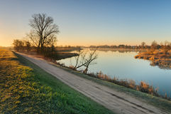 Road on the shore of a wild pond next to a village during sunrise in autumn morning Stock Photos