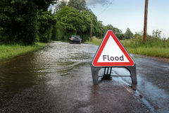 Road side flooded sign. County road in essex of flooded road closed due to severe rain with car stuck in the middle of road royalty free stock photography
