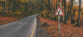 Road sigh. Road between autumn forest trees  Road sign - turn right Stock Images