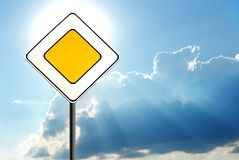 Road sign. In sun beams against clouds Royalty Free Stock Photo