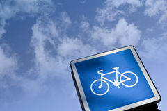 Road sign. Bike on a road sign, cloudy sky on background Stock Image