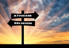 Road sign atheism and religion at sunset Stock Photos