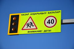 Road sign ATTENTION CHILDREN in Kazakh and Russian. Road sign ATTENTION CHILDREN against the background of the blue sky royalty free stock photography