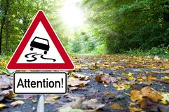 Road sign with attention slippery when wet stock photo