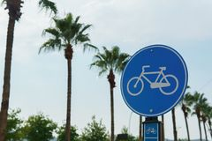 Road sign of a bike path against a background of clear sky and palms Royalty Free Stock Photography