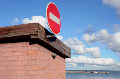 Road sign brick on building. Pier and sea distance Stock Photography