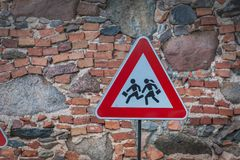 Road sign caution children over stone wall background. stock photo