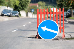 Road sign at city street due a pothole Royalty Free Stock Photo