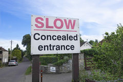 Road Sign Concealed Entrance. A Road Sign saying Slow Concealed Entrance Stock Photo