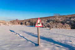 Road sign concept steep turn, close-up. Snow-covered road in the countryside with road sign challenges ahead royalty free stock photo