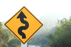 Road sign beside curve mountain road Royalty Free Stock Photos