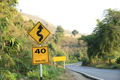 Road sign beside curve mountain road Royalty Free Stock Photography