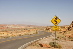 Road Sign for Curves in Desert. A road sign in the middle of a desert showing curves ahead Royalty Free Stock Photos