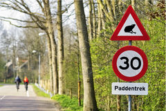 Road sign with cyclists in the background Royalty Free Stock Images