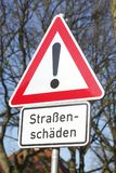 Road Sign danger place. Street damages with blue sky Stock Image