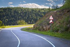 Road sign dangerous turn. Installed near the road leading to mountains and forests royalty free stock image