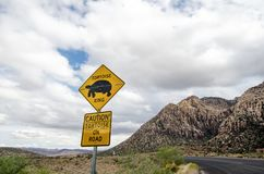 Road sign for desert tortoise turtle crossing, warning drivers of the animal presence. On road royalty free stock photo
