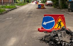 Road sign, detour, road repair on the background of the road and broken asphalt pieces Stock Image