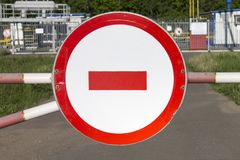Road sign do not enter on a barrier against industrial object. Restricted area in Russia. royalty free stock photos