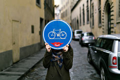 Road sign in the face. Road sign with a bicycle and lips in the face Stock Photos