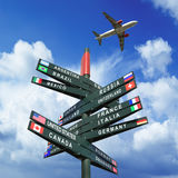 Road sign with flags from countries, plane in the sky Stock Photography