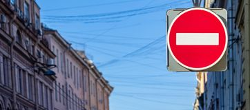 Road sign the forbidding entrance. One big road sign the forbidding entry is located a closeup against the background of a part of a city landscape stock image