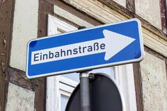 Road sign for one-way street. Road sign with german text: one-way street in front of a half-timbered house Royalty Free Stock Photos