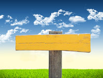 Road sign in green grass field. Over blue sky background Royalty Free Stock Photos