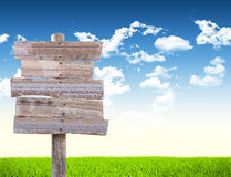 Road sign in green grass field. Over blue sky background Royalty Free Stock Image