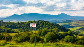Road sign on the hillside. Mountain ridge  with Pikui peak in the distance. Carpathian travel destination concept. location Volovets, TransCarpathia, Ukraine Royalty Free Stock Image