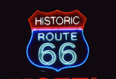 Road Sign for Historic Route 66. This is a road sign that says Historic Route 66. It is a neon sign in red, white and blue against a black night sky Stock Photography