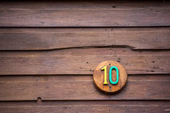 Road sign on a house reading the number ten made out of wood. On a round wooden base. Sign is situated in the lower right hand part of the photo. Painted in stock photos