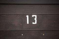 Road sign on a house reading the number thirteen painted with white paint on wooden panel Stock Photos