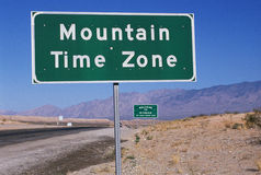 Road sign indicating Mountain Time Zone. This is a road sign indicating a change to the Mountain Time Zone. The sign is green against a blue sky Royalty Free Stock Images