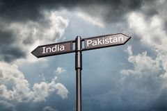 Road sign with the inscription India, Pakistan against the backdrop of a stormy sky.  royalty free stock image