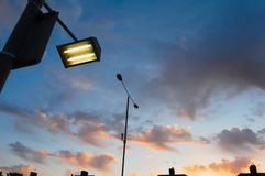 Road sign lamp pictured against dramatic sunset sky in suburbia royalty free stock images
