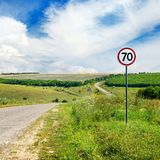 Road sign limiting speed on a road. Royalty Free Stock Image